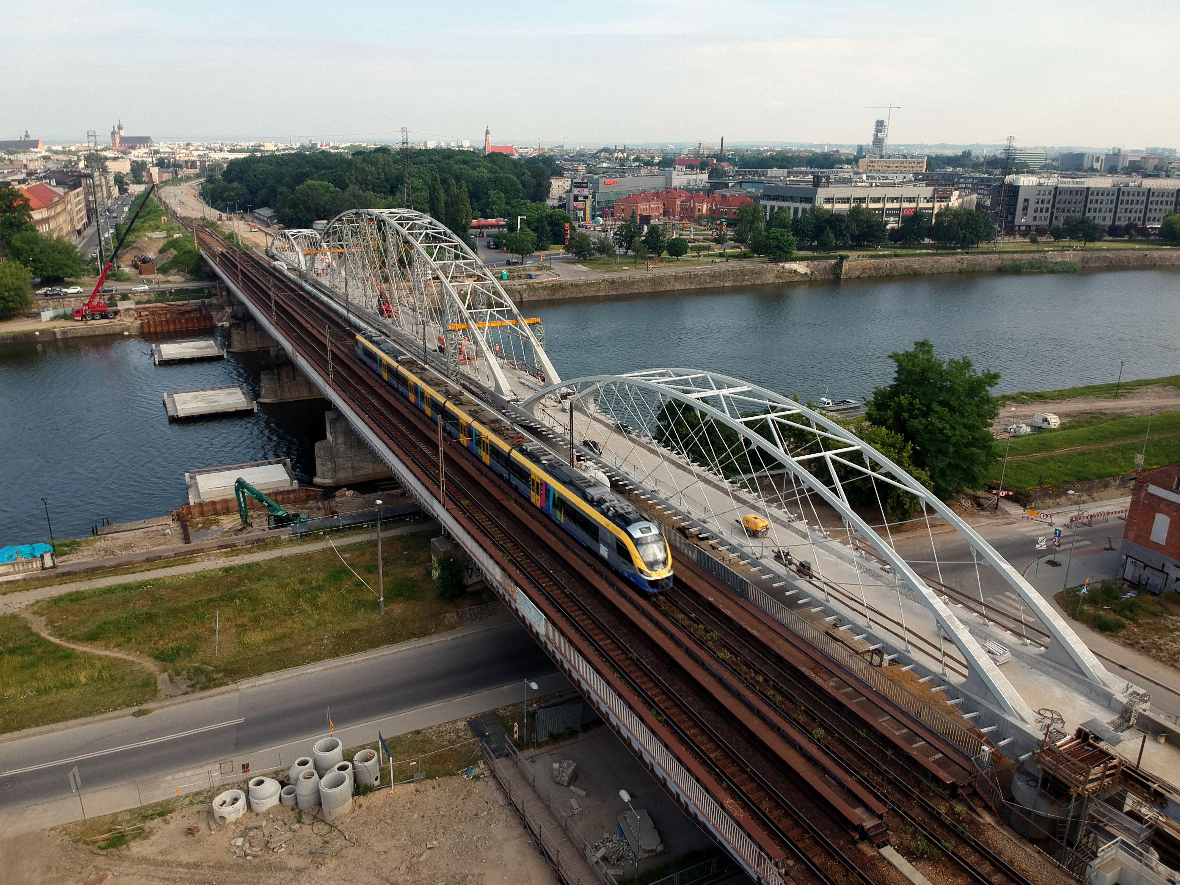 Zdjęcie przedstawiające stary i nowy most kolejowy na Wiśle w Krakowie.