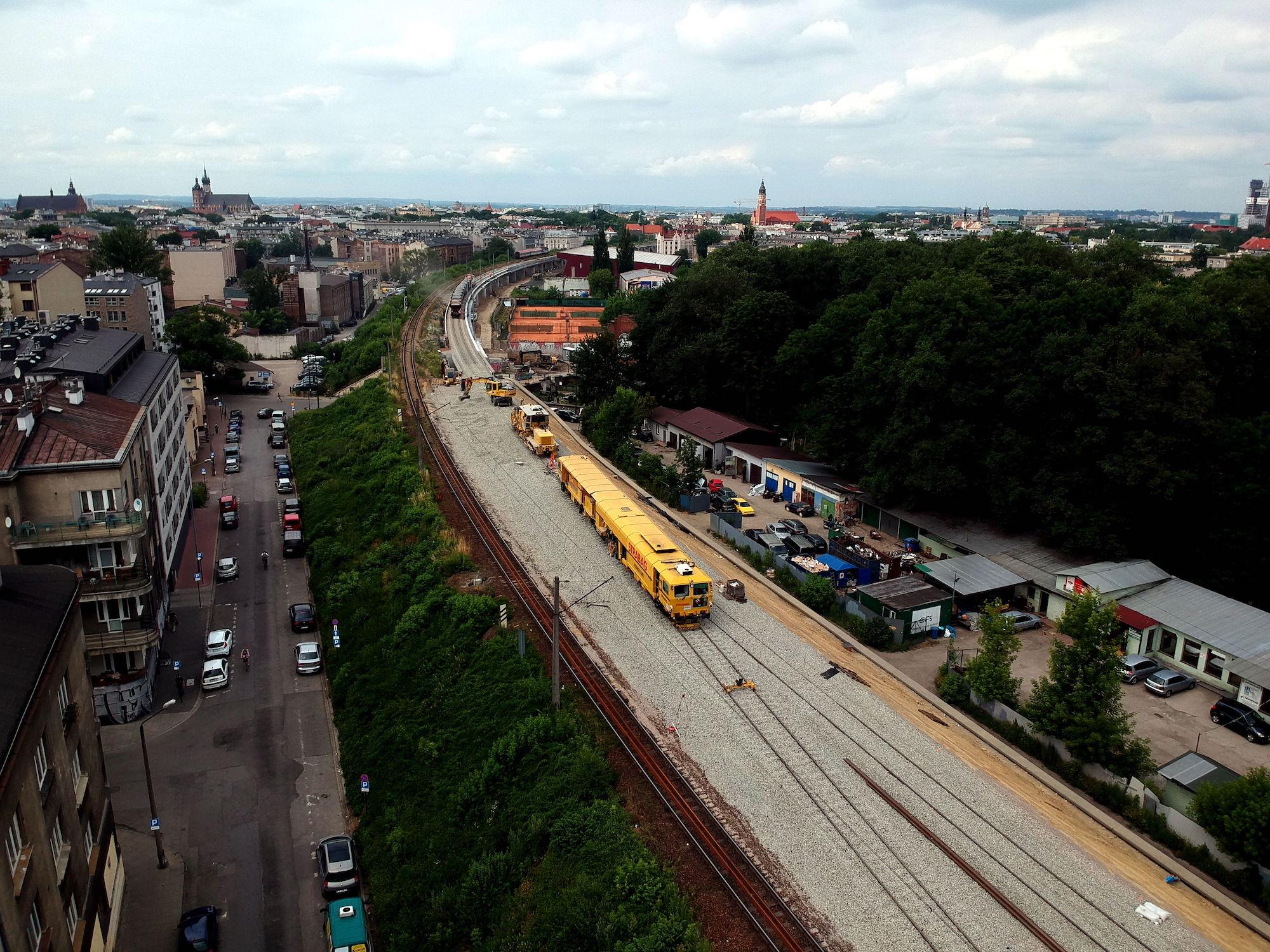 Zdjęcie lokomotywy na torach na estakadach w centrum Krakowa.