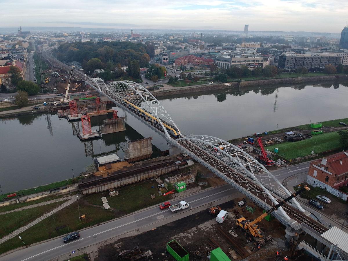 Zdjęcie z powietrza przedstawia nowy most kolejowy na Wiśle w Krakowie oraz podpory, pozostałe po demontażu starego mostu.